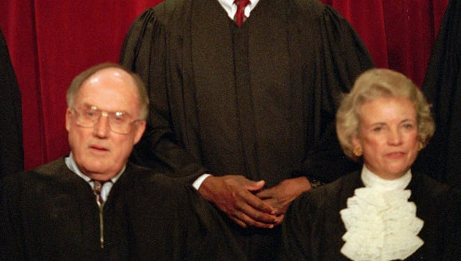 Associate Supreme Court Justice Clarence Thomas laughs while posing with other court members for a portrait on Nov. 10, 1994, at the court in Washington. Chief Justice William Rehnquist and Associate Justice Sandra Day O'Connor are in the front row.