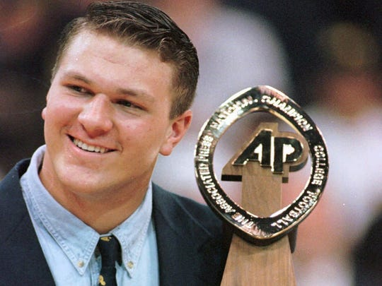 Michigan offensive lineman and co-captain John Jansen holds The Associated Press National Championship trophy Saturday, Jan. 3, 1998, after it was presented to him during halftime at the Michigan basketball game against Penn State in Ann Arbor, Mich.