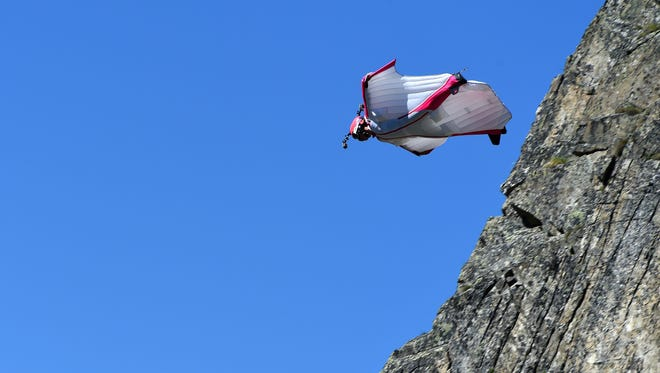 Switzerland's Geraldine Fasnacht jumps from the top of the Brevent mountain to fly in wingsuit over the French ski resort of Chamonix on July 16, 2014.   AFP PHOTO / PHILIPPE DESMAZES        (Photo credit should read PHILIPPE DESMAZES/AFP/Getty Images)