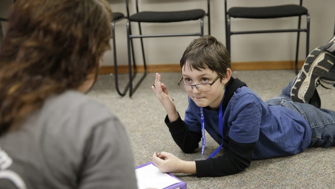 Jennifer Leanna of the Center for Autism and Related Disorders, left, works with client Connor Drogos, 9, in Leanna's De Pere office.