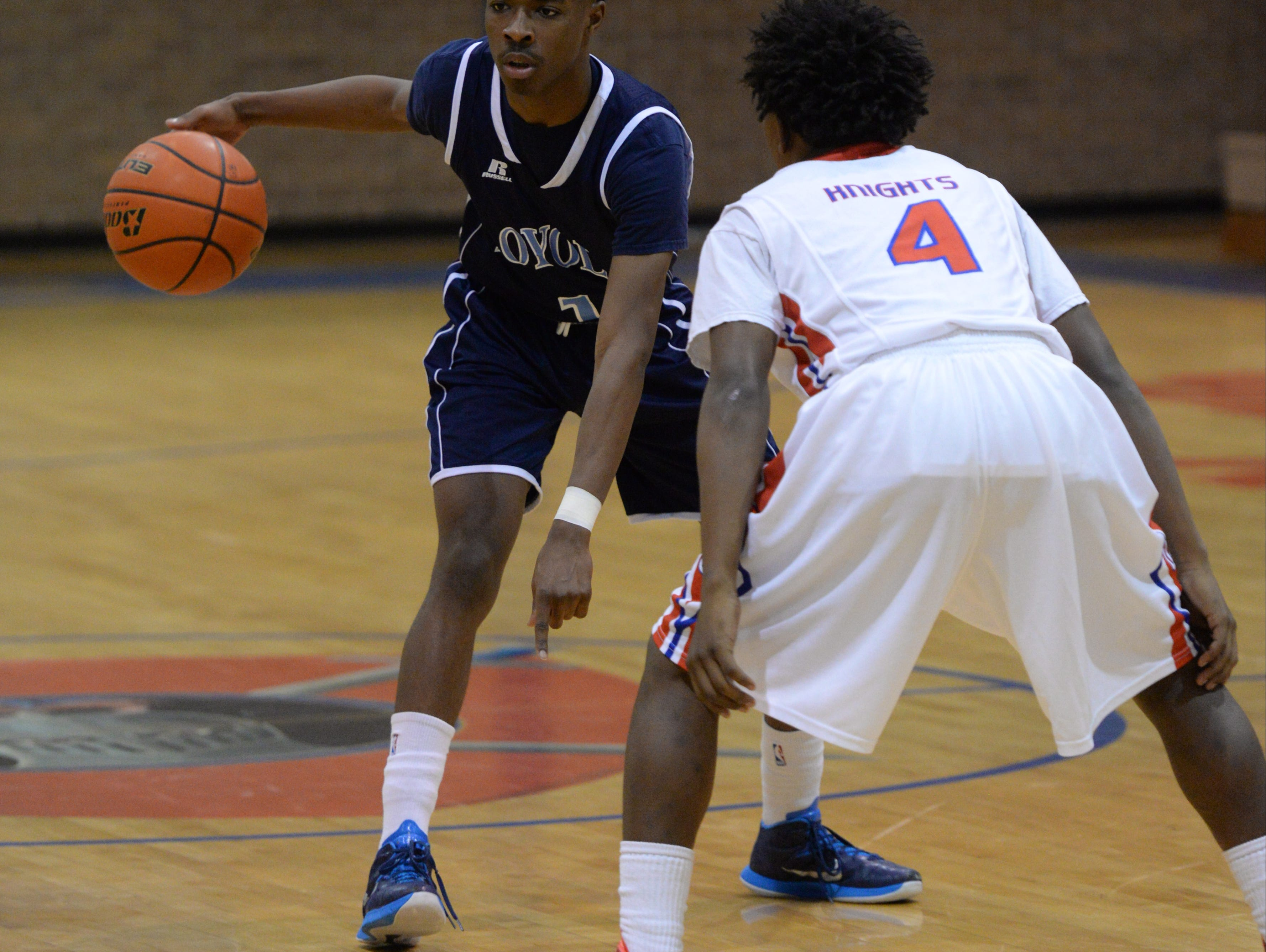 Loyola's Tony Dorsey motions to a teammate while being guarded by Woodlawn's Cam Moore.