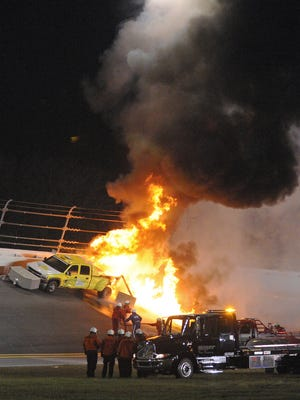 Emergency workers try to extinguish a fire on a jet dryer during the NASCAR Daytona 500 on Feb. 27, 2012.
