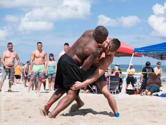 Beach Nationals champion Jacob Kasper of Lexington attacks the legs of runner-up Charles Daniels at Carolina Beach, N.C.
