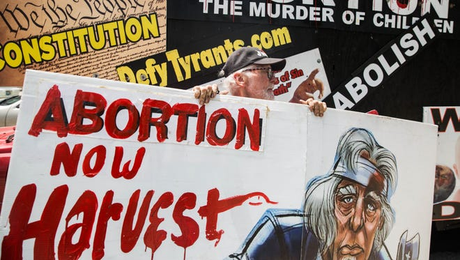 Ronald Brock, Missionary to the Preborn, holds signs protesting the proposed buffer zone around Kentucky's last abortion clinic. July 19, 2017.