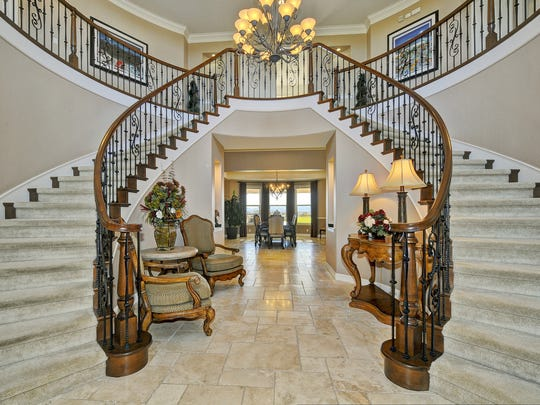 The entrance leads to a breathtaking entryway, with a dramatic symmetrical double staircase on either side.