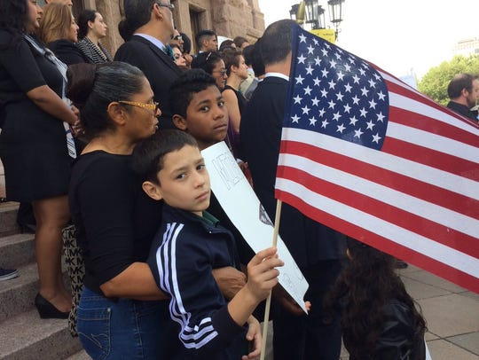 Isaac Lopez, 8, holds an American flag at the protest
