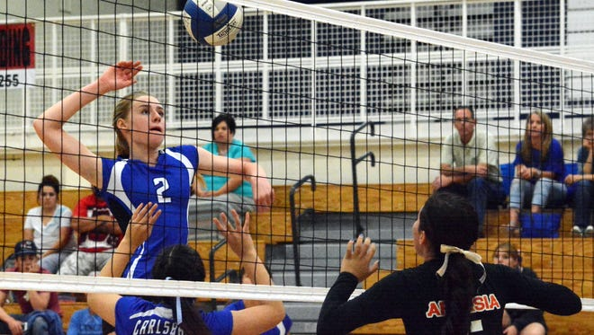 Carlsbad freshman middle blocker Carrie Lynn gets a quick kill down the middle in the first set Tuesday.
