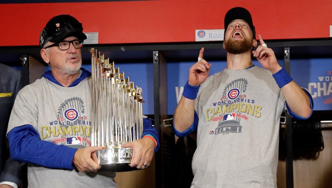 Cubs manager Joe Maddon holds the World Series trophy and celebrates with Series MVP Ben Zobrist early Thursday morning after winning Game 7 in Cleveland.