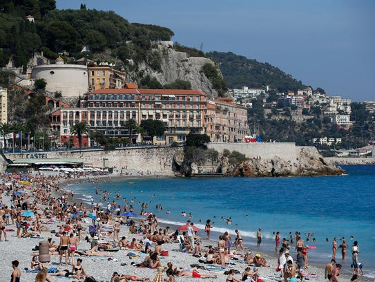 People enjoy the sun and the sea on a beach in Nice,