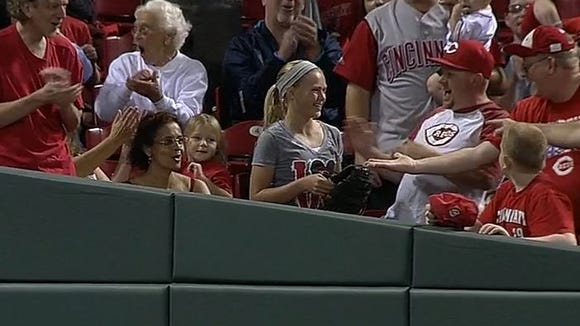 A Reds fan (center) caught a foul ball over the rail in the ninth inning, resulting in a replay that ultimately found no fan interference.