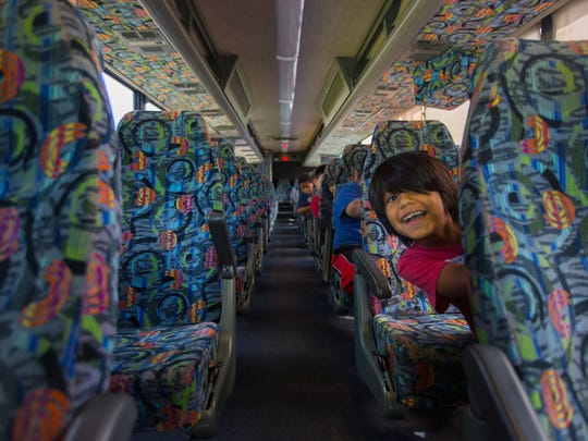 Jose Infante plays with other children on the bus as they wait their turn to be fitted for shoes at Snyderman's Shoes of Naples on Monday, Aug. 1, 2016.