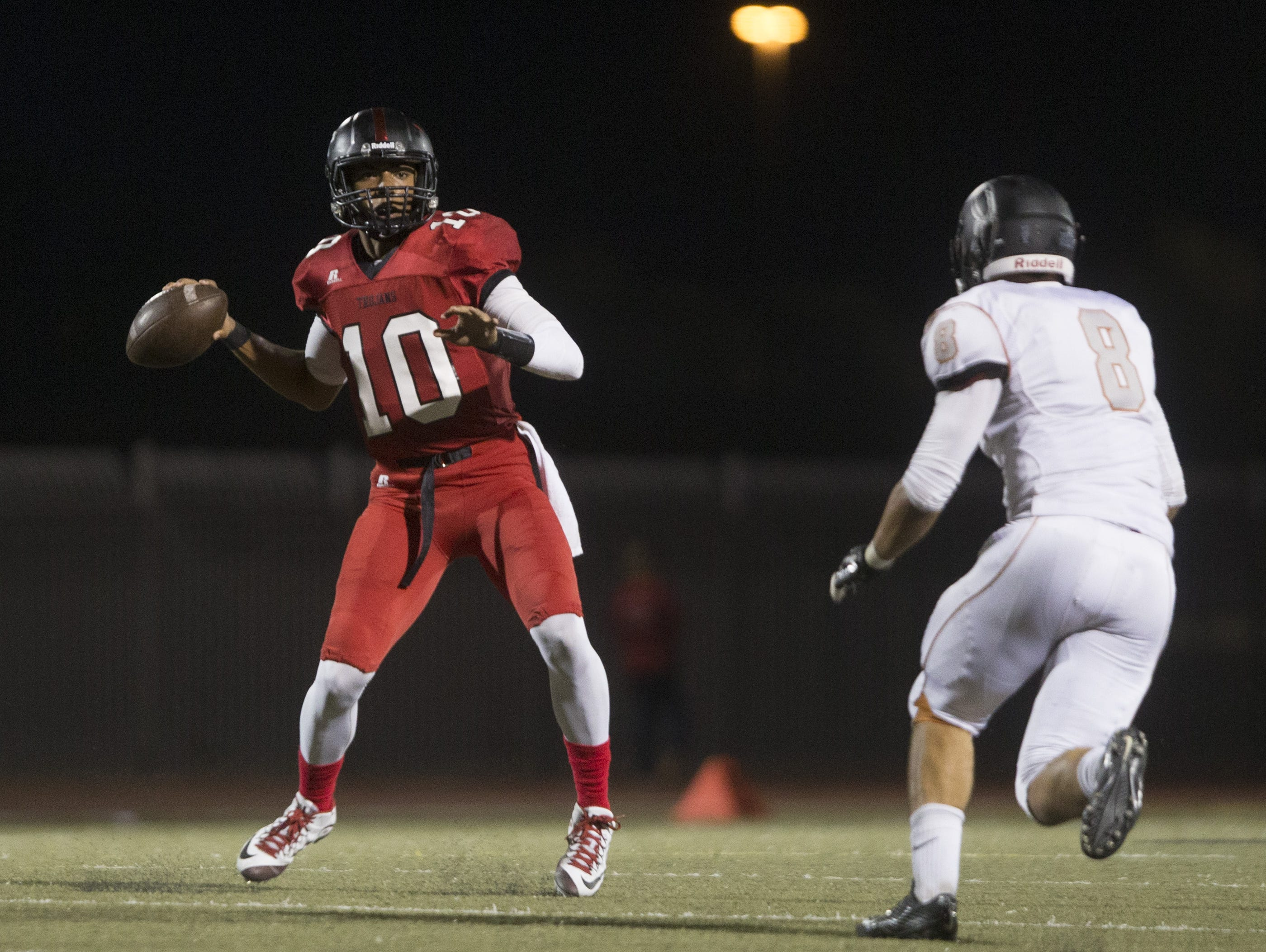 Paradise Valley's Daniel Bridge-Gadd escapes pressure from Desert Edge's Alex Aguirre (8) before running for a first down at Paradise Valley High School in Paradise Valley, AZ on September 3, 2015.