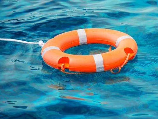 Orange life preserver laying in the water.