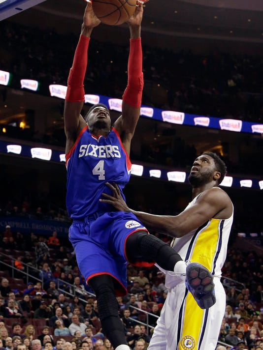 Philadelphia 76ers' Nerlens Noel, left, dunks the ball against Indiana Pacers' Roy Hibbert during the first half of an NBA basketball game, Saturday, Jan. 10, 2015, in Philadelphia. (AP Photo/Matt Slocum)