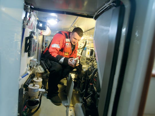 Lt. Richard Russell of Coast Guard Sector Puget Sound inspects a fire extinguisher in the engine room of the vessel owned by Gene and Martha Paxton of Bremerton during a safety inspection.