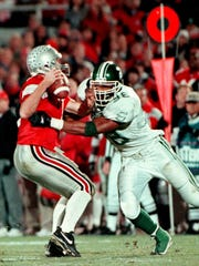 MSU's Julian Peterson (98) sacks Ohio State's quarterback Joe Germaine in the fourth quarter which resulted in a fumble that MSU recovered.