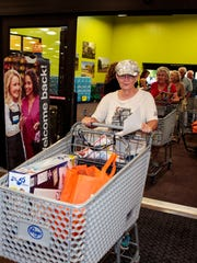 Jeanna Ward leads a parade of shoppers into the newest Kroger, located on Veteran's Parkway.  Ward arrived at the store at 6 a.m. Wednesday, Aug. 31, 2016, to assure her  spot in line for the grand opening.