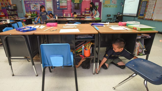 Second-graders hide under their desks for cover during the annual Great Guam ShakeOut earthquake drill at Agana Heights Elementary School on Thursday, Oct. 20.