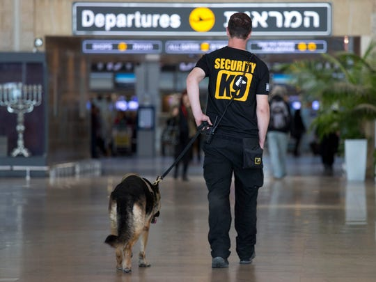 An Israeli airport security guard patrols with a dog