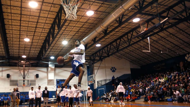 Quan Patterson dunks during Godby High School's celebration of their undefeated run to the state title on Friday in the school's gymnasium.