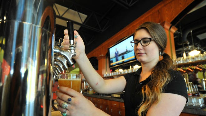 Manager Shelby Champagne, 22, of Wausau, pours a cup of beer at Red Eye Brewing Company in Wausau.