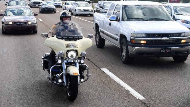 A member of the Tennessee Highway Patrol rides his motorcycle on US HWY 45 Bypass during the state-wide Distracted Driving Enforcement Bus Tour, Monday, October 9.