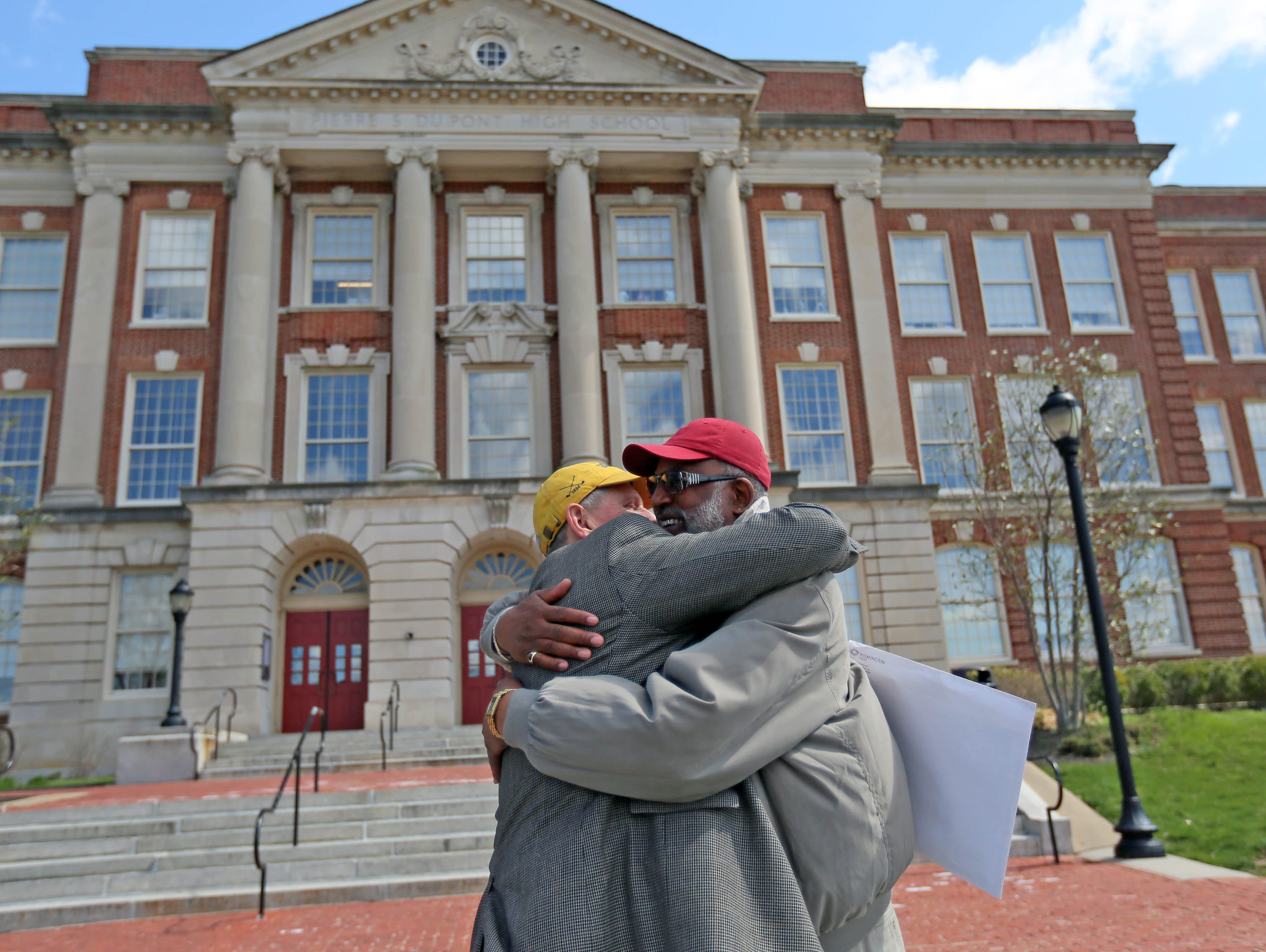 Randy Johnson gives a big hug to his former 1968 basketball teammate Ron Smith in front P.S. du Pont High School.