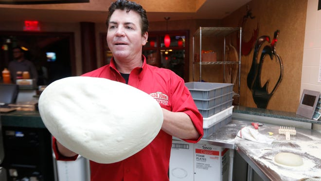 John Schnatter, founder of Papa John's Pizza, tosses a pie in the kitchen at the company's headquarters in Louisville, Kentucky.