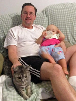 Daddy Duty columnist Tim Walters relaxes while feeding Isabella and petting Vapor.