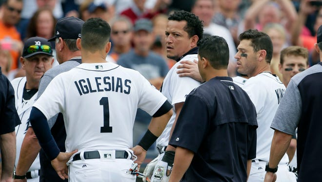 Tigers designated hitter Miguel Cabrera looks back at the Yankees as he is guided off the field by teammate Ian Kinsler, right, and Jose Iglesias (1) following a bench-clearing fight during the sixth inning of the Tigers' 10-6 win on Thursday, Aug. 24, 2017, at Comerica Park.