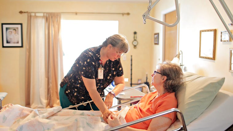 Hospice Nurse Rene Lowry checks the pulse of Janice