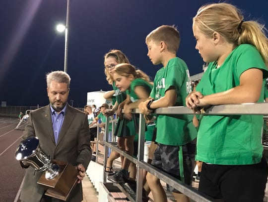 UIL Director of Music Dr. Bradley Kent shows the Lone Star Cup to a group of young Wall High School football fans before halftime of the football game Friday, Sept. 1, 2017, at Hawk Stadium in Wall.