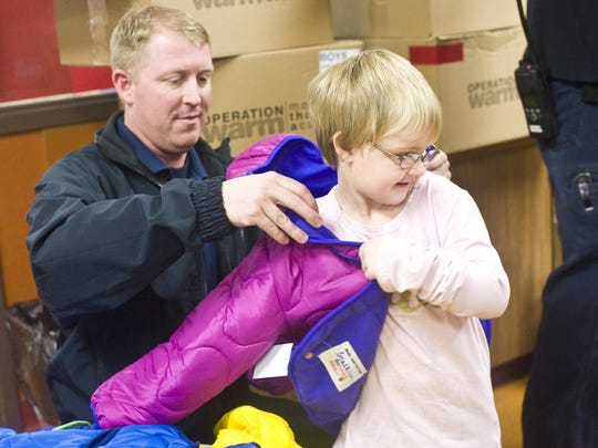Firefighter J.D. Kulbeck helps Gracelyn Meadows, 4, put on a coat during an Operation Warm event for Head Start children at Skyline School on Tuesday.