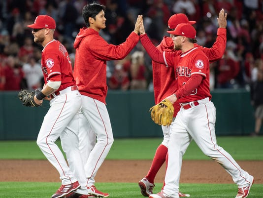 Los Angeles Angels' Shohei Ohtani, center, celebrates the team's 13-9 win over the Oakland Athletics with his teammates at the end of the baseball game, Friday, April 6, 2018, in Anaheim, Calif. (AP Photo/Kyusung Gong)