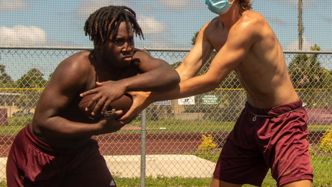 St. Augustine quarterback Sammy Edwards, right, works on the mesh point with running back Sean Harvey during a June 15 workout at St. Augustine High School. Monday was the first day St. Johns County programs could hold workouts since the Florida High School Athletic Association suspended varsity sports in the state on March 18.