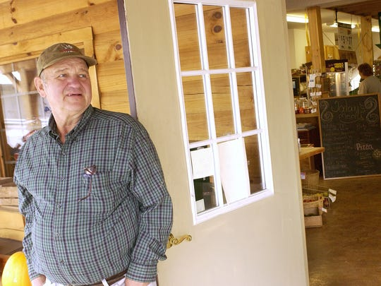 Business continues inside as co-owner Wade Burks stands outside the front door of the Greenville Trading Post in Greenville on Friday, Oct. 14, 2005.