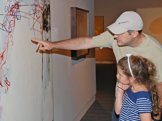 Brian LeGros and his daughter Emily look over a painting