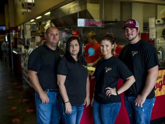 Restaurant owners Bryan and Chantell Aucoin, CEO Brittani Aucoin, and COO Ian Neuville pose for a photograph at the Hot Dawg Stop in Youngsville, La., Friday, July 10, 2015.