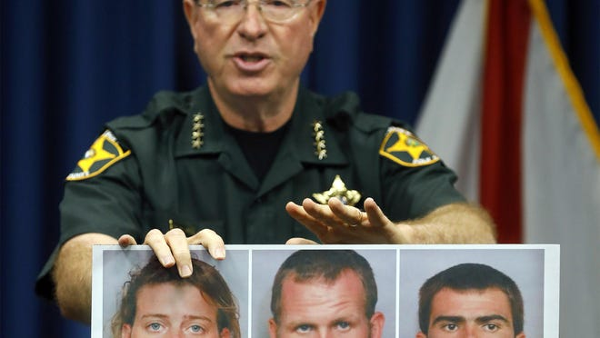 "Sheriff Grady Judd holds pictures of Mary Whittemore, Tony ""T.J."" Wiggins and William ""Robert"" Wiggins -- the suspects charged for their roles in the killings of Brandon Rollins, Damion Tillman and Keven Springfield -- during a media briefing at the Polk County Sheriff's Office in Winter Haven Wednesday."