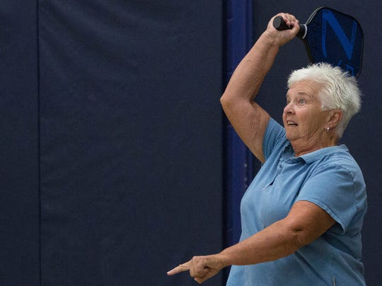 Sue Williams watches the ball fly over the net as she follows through with her swing, during a pickleball match at Meerscheidt Recreation Center.