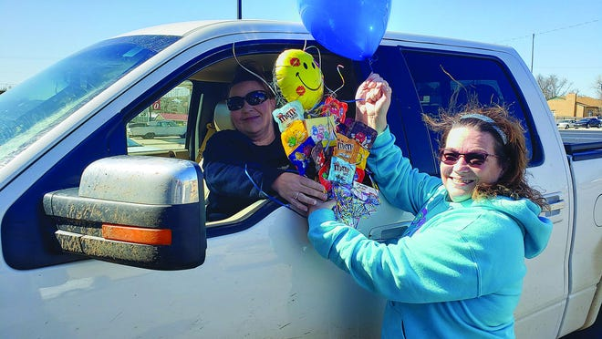 """Balloons and More, Inc. owner Tonja Harrison delivers a """"just because"""" M&M balloon bouquet to Taunya Westerman, providing a """"to the car"""" service. Harrison said she is pulling out all the stops  when it comes to providing services to customers which will also help keep her business afloat in this time of dealing with coronavirus restrictions."""