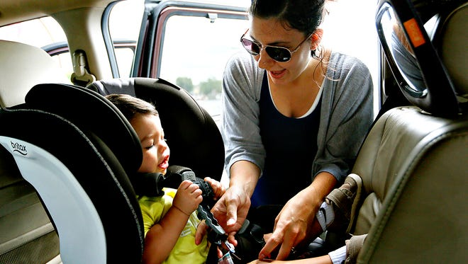 Stevie Hoff, of Dover Township, secures her 18-month-old son, Titan Hoff, in his rear-facing car seat in the West Manchester Township Target parking lot Wednesday, Aug. 10, 2016. Dawn J. Sagert photo