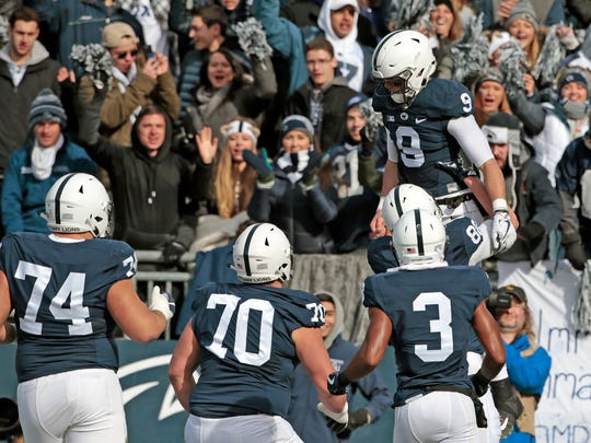Penn State quarterback Trace McSorley (9) is lifted in the air by teammate Mike Gesicki (88) after scoring a touchdown against Rutgers during the first half of an NCAA college football game in State College, Pa., Saturday, Nov. 11, 2017. (AP Photo/Chris Knight)