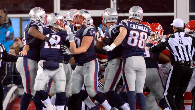 New England Patriots quarterback Tom Brady (12) is held back by teammates after scoring a touchdown during the second quarter against the Kansas City Chiefs in the AFC Divisional round playoff game at Gillette Stadium.