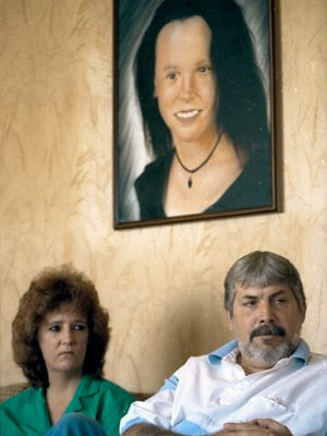 Georgia and Mickey MacNeir sit underneath a portrait of their daughter and step-daughter respectively, Jennifer Persia, who was found stabbed to death in her Magnolia home.