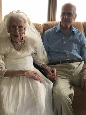 Arleen and Forrest Meyer hold hands while having their picture taken. Arleen put on her wedding dress from 75 years ago.