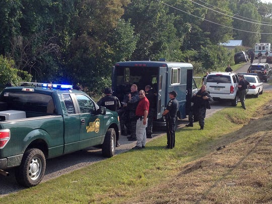 Law enforcement officials line Chester Hill Road during a standoff July 31.