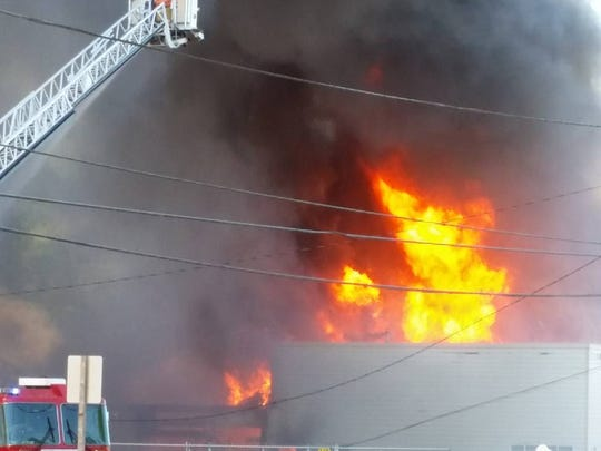 """Flames shoot from a building in Turner Sunday, May 1, as fire crews work to contain a five-alarm fire. """"It was amazing watching these guys work,"""" said Drea Rasmussen."""