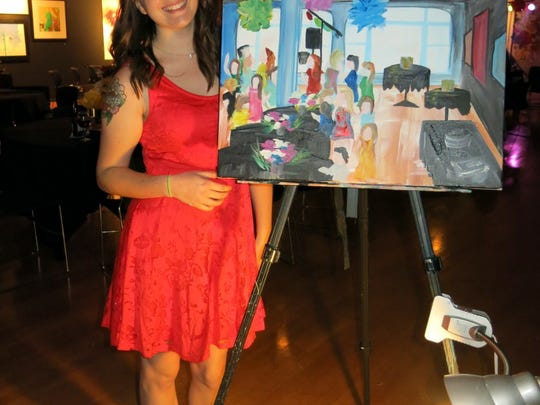 """Artist Caitlin Lindsay with her rendering of """"A Night With the Debs"""" party  she drew as the party progressed at artspace. The party honored Demoiselle Debs Courtney Ann Prestwood and Brooke Shemwell."""