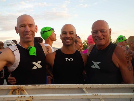 Triathlete Ken Pagliughi (right) poses with his teammates